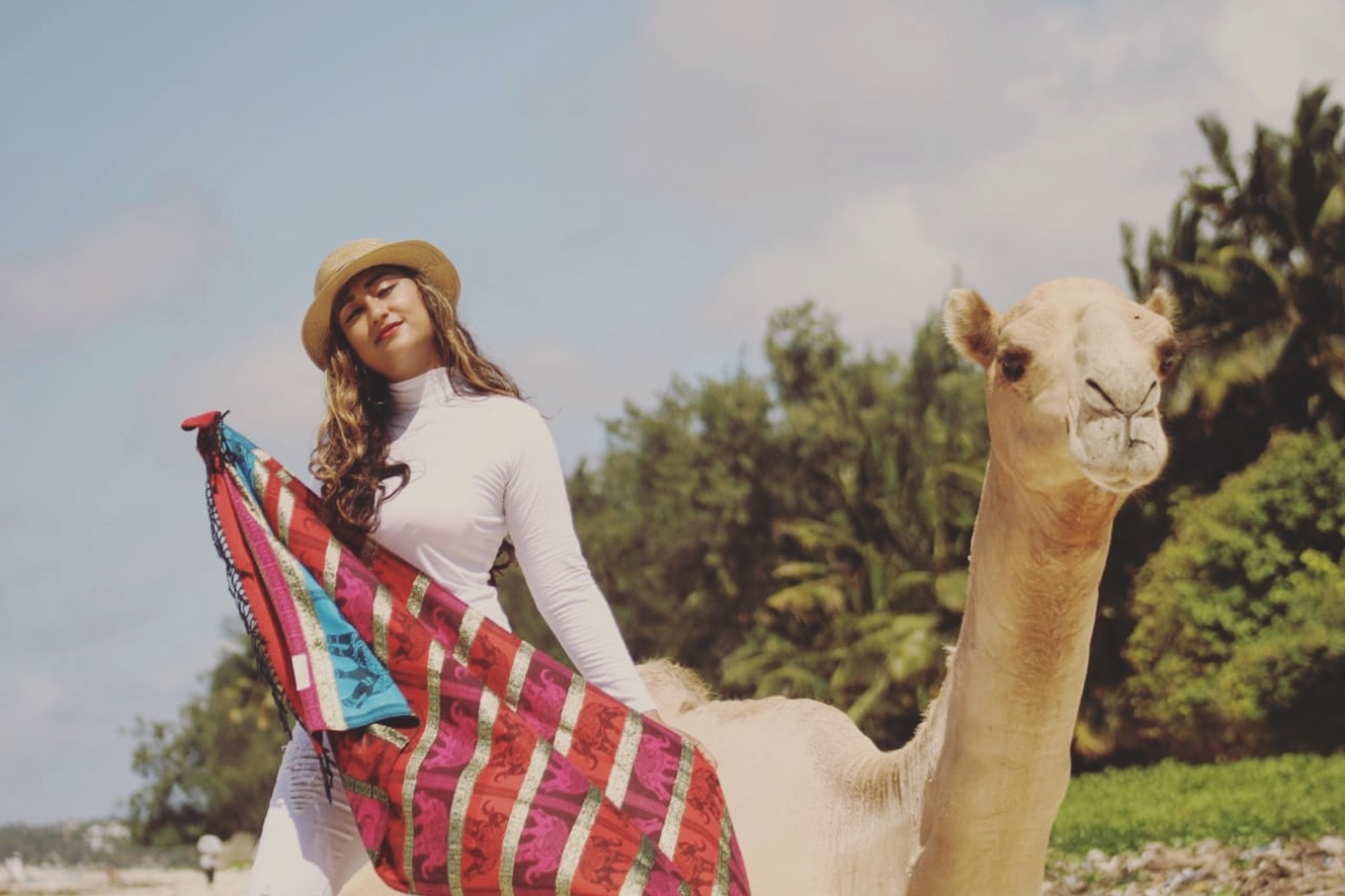 selective focus photography of woman standing beside brown camel during daytime
