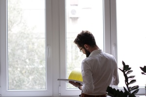 man reading book in front of window