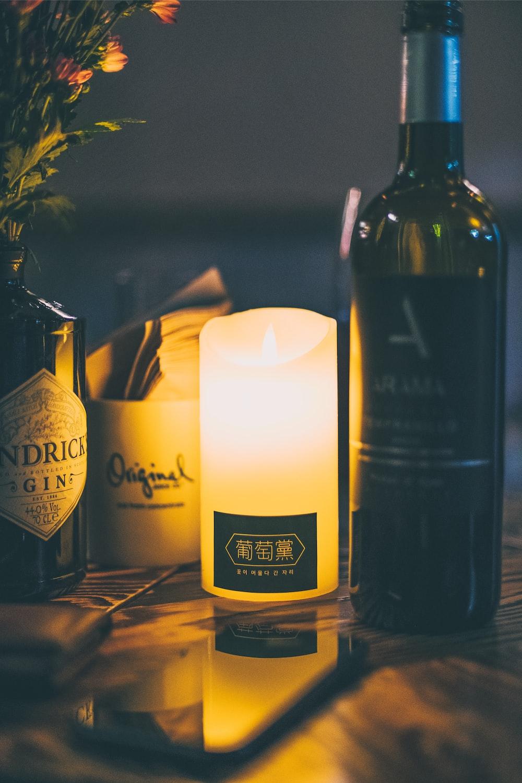 white pillar candle beside wine bottle