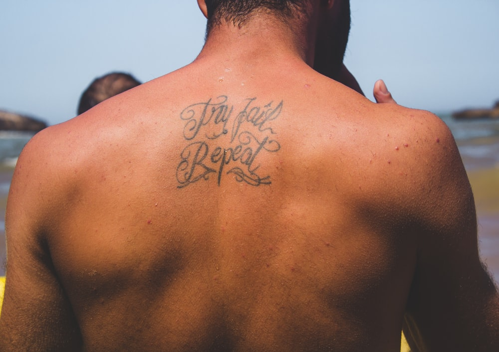 person with try fail repeat tattoo at back