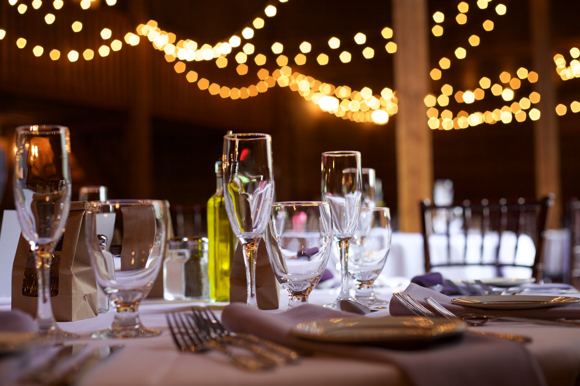 A table set for a fancy occasion; plates, glasses, silverware and napkins are all shown.