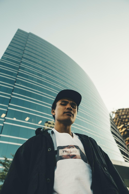 man standing beside high-rise building