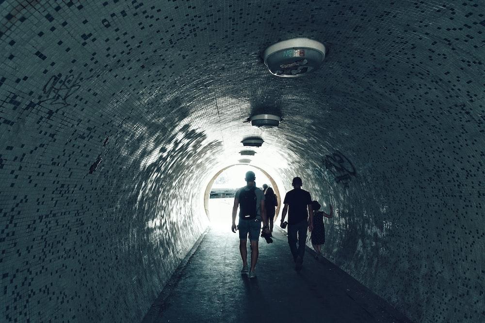 people walking under tunnel