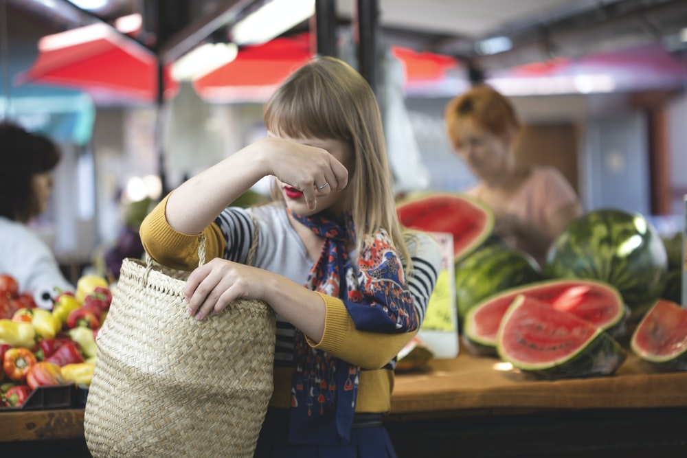 woman carrying woven bag in market