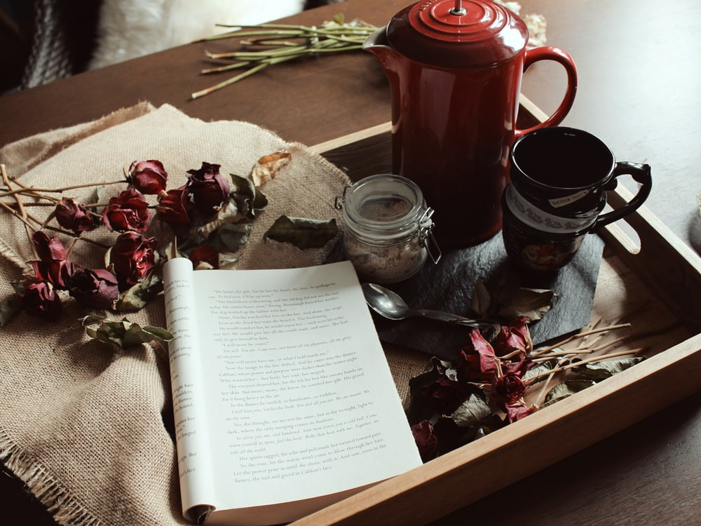 opened book near spoon, flowers, mug and pitcher on tray