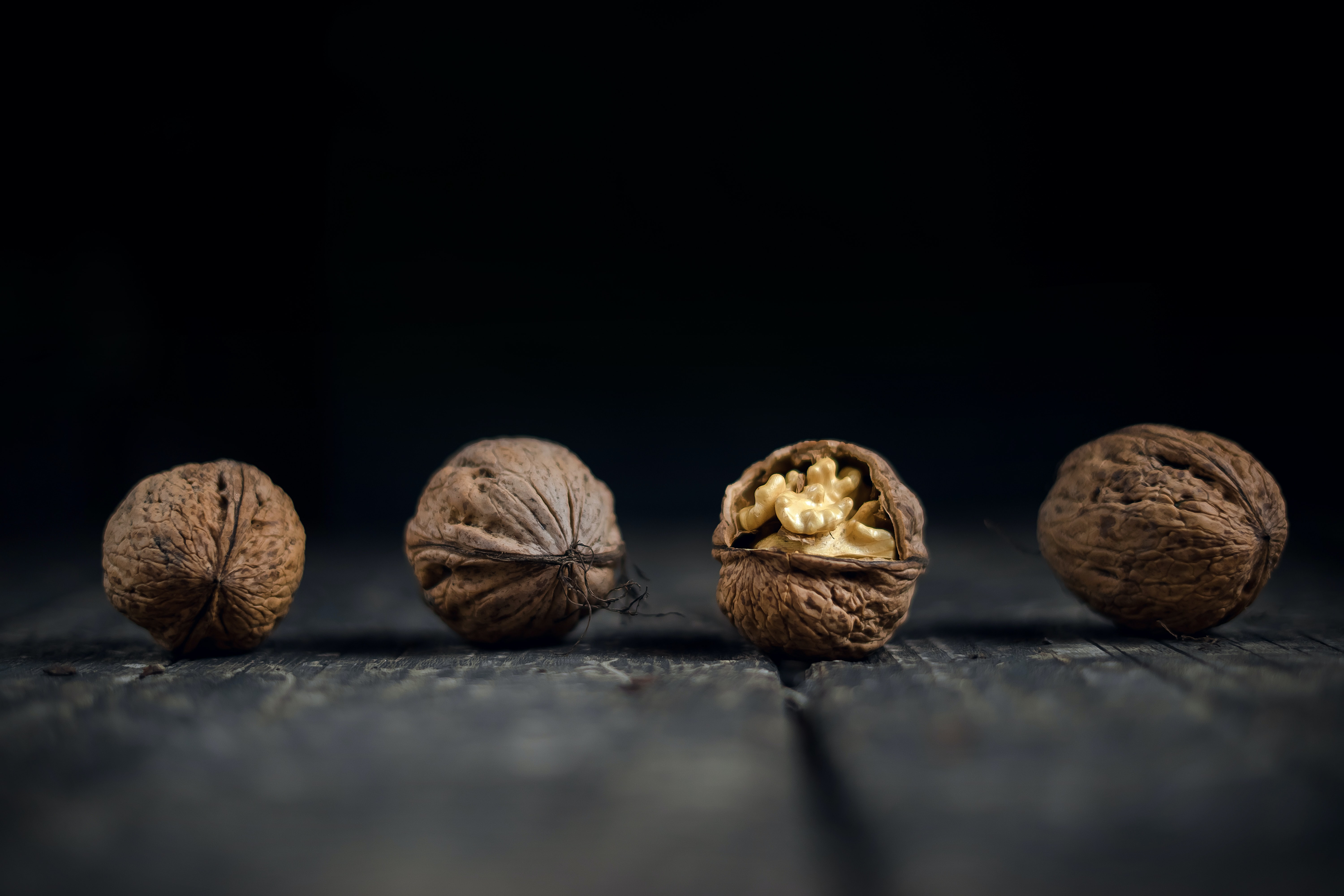 close-up photo of four brown walnuts
