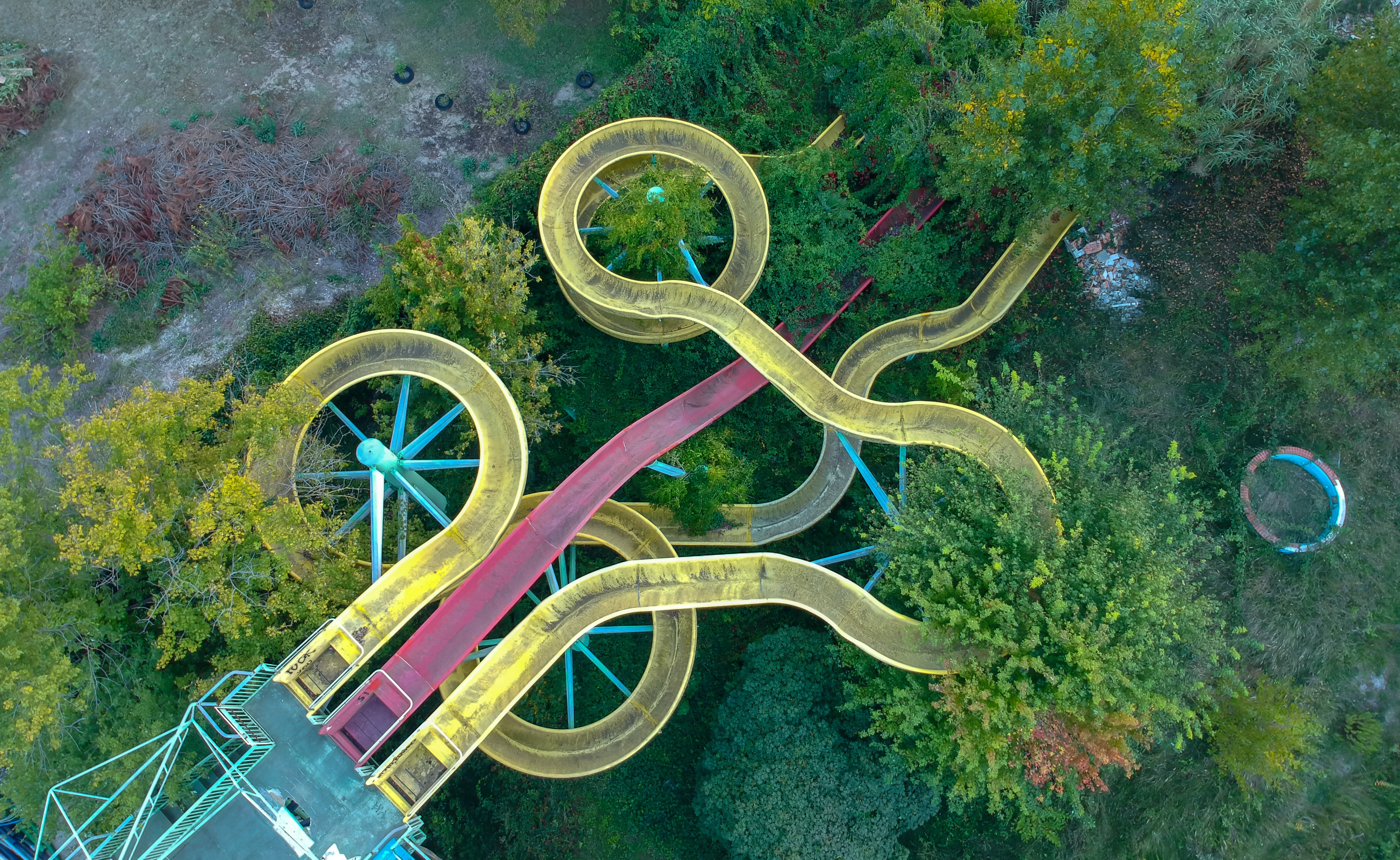yellow and red metal slides surrounded by green trees at daytime