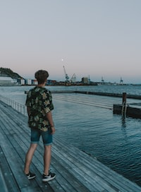 man standing on dock near sea