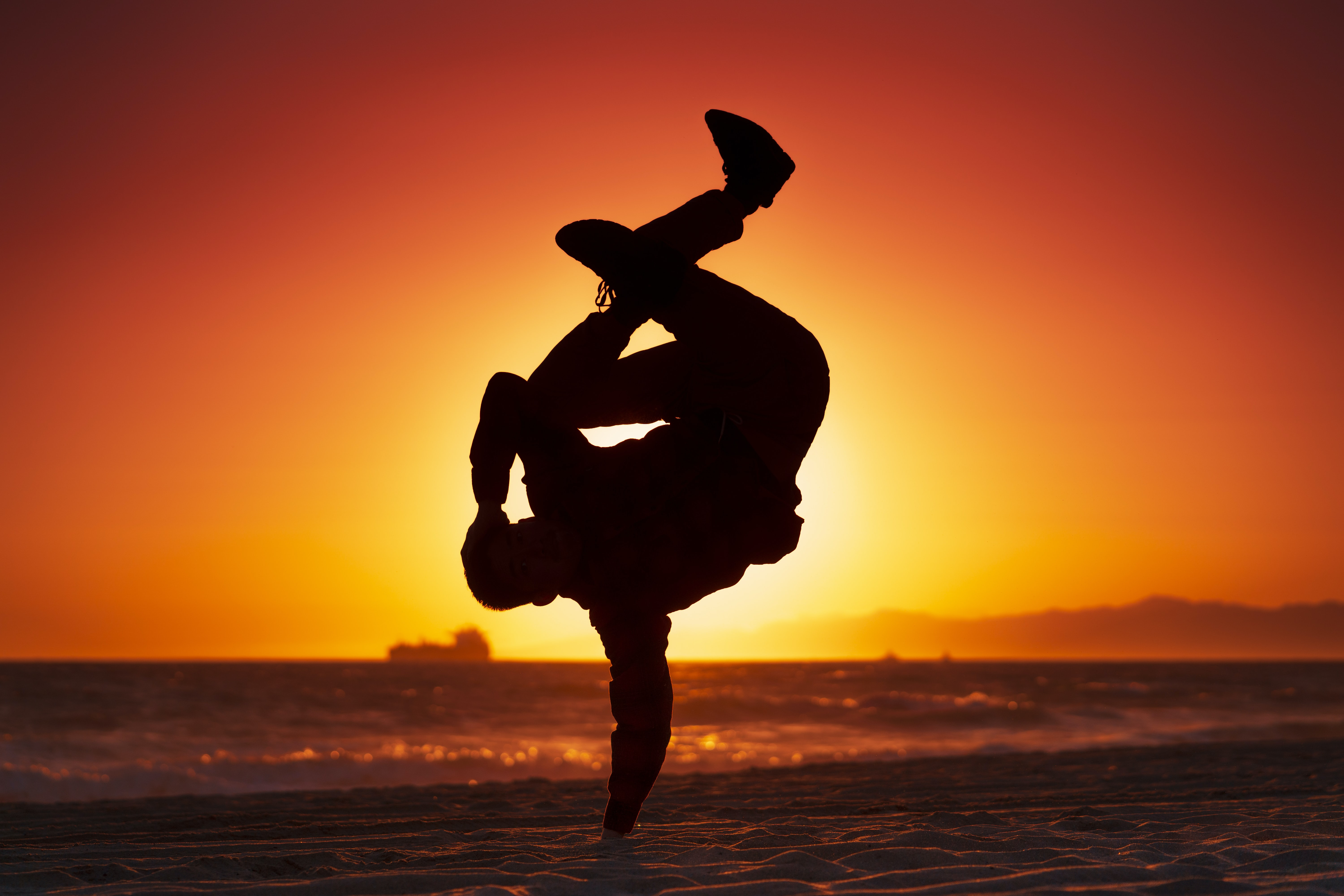 silhouette of man making a handstand