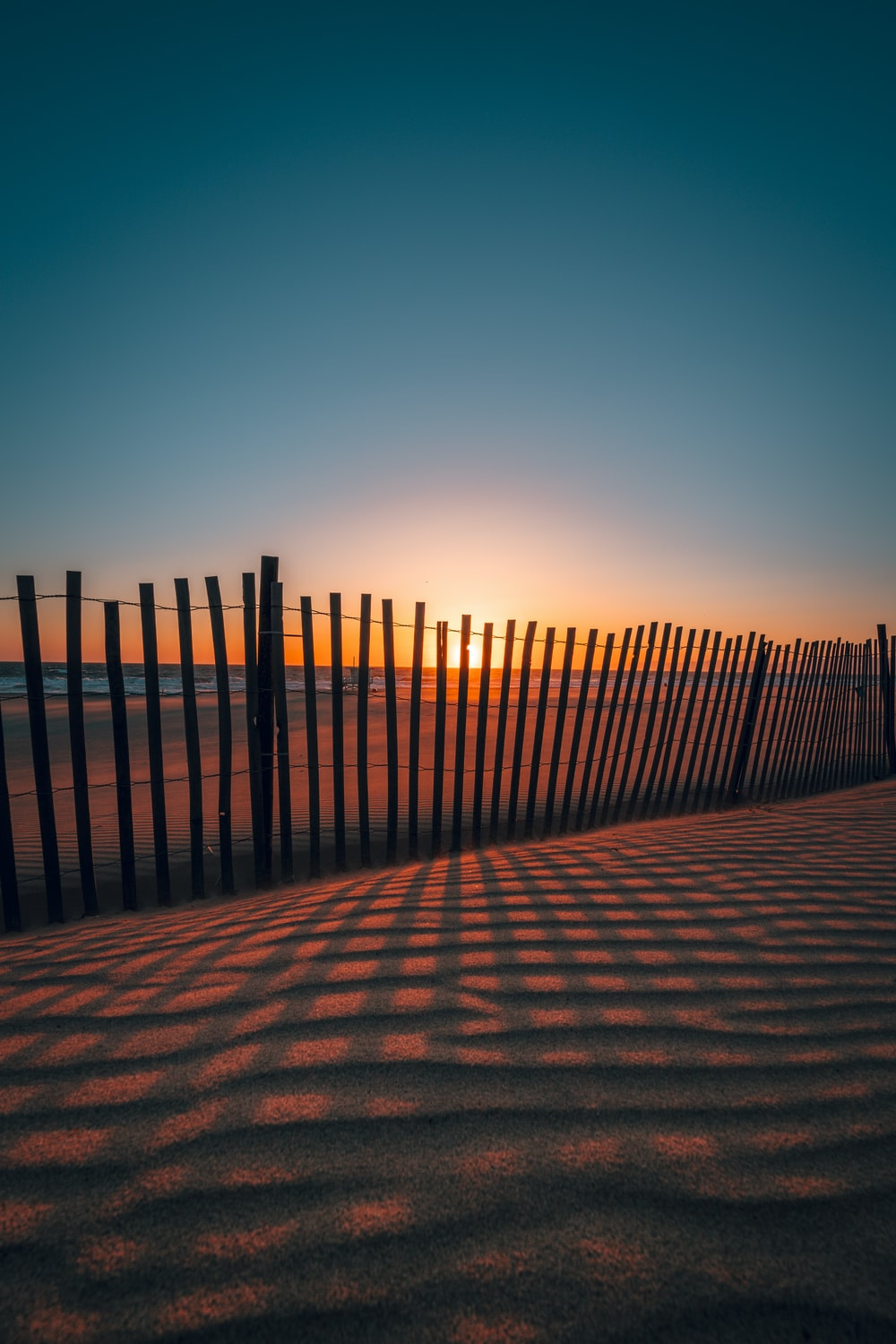 sunset as seen through brown wooden fences