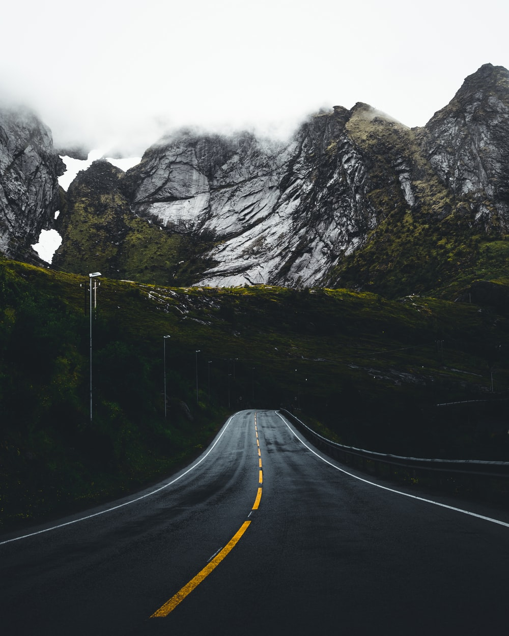 asphalt road leading to mountains