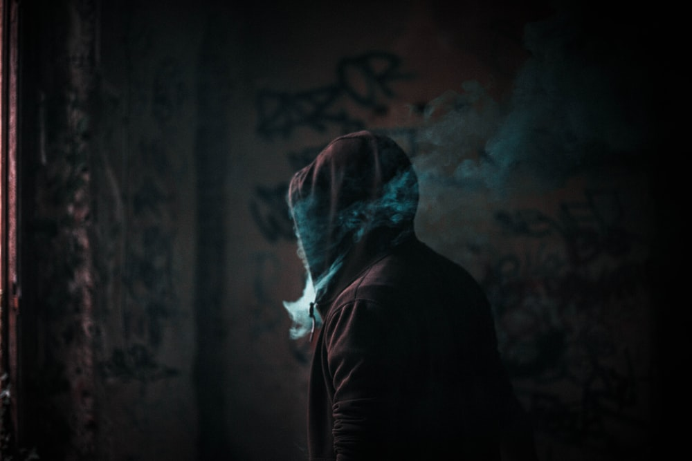 person in hoodie smoking