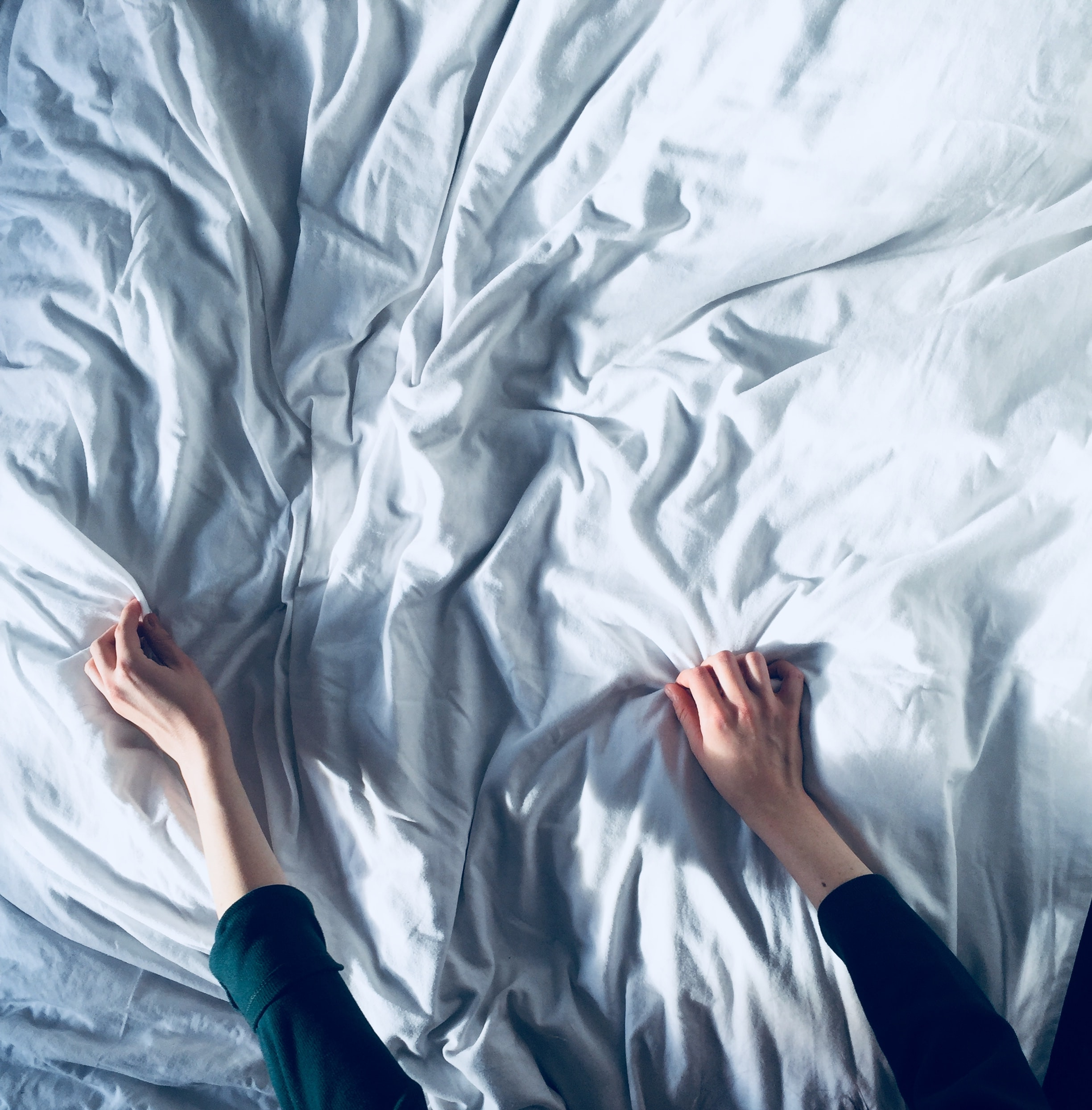 person holding white bedspread