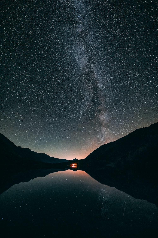 reflection photography of lake under black sky