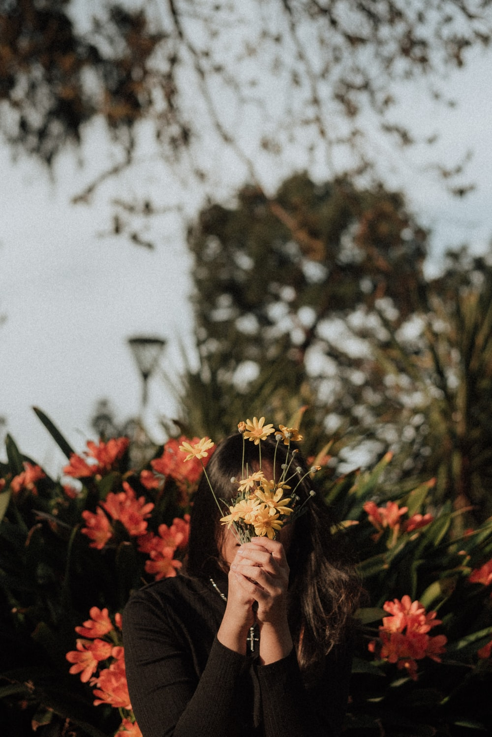 woman hiding her face with yellow flowers during daytime