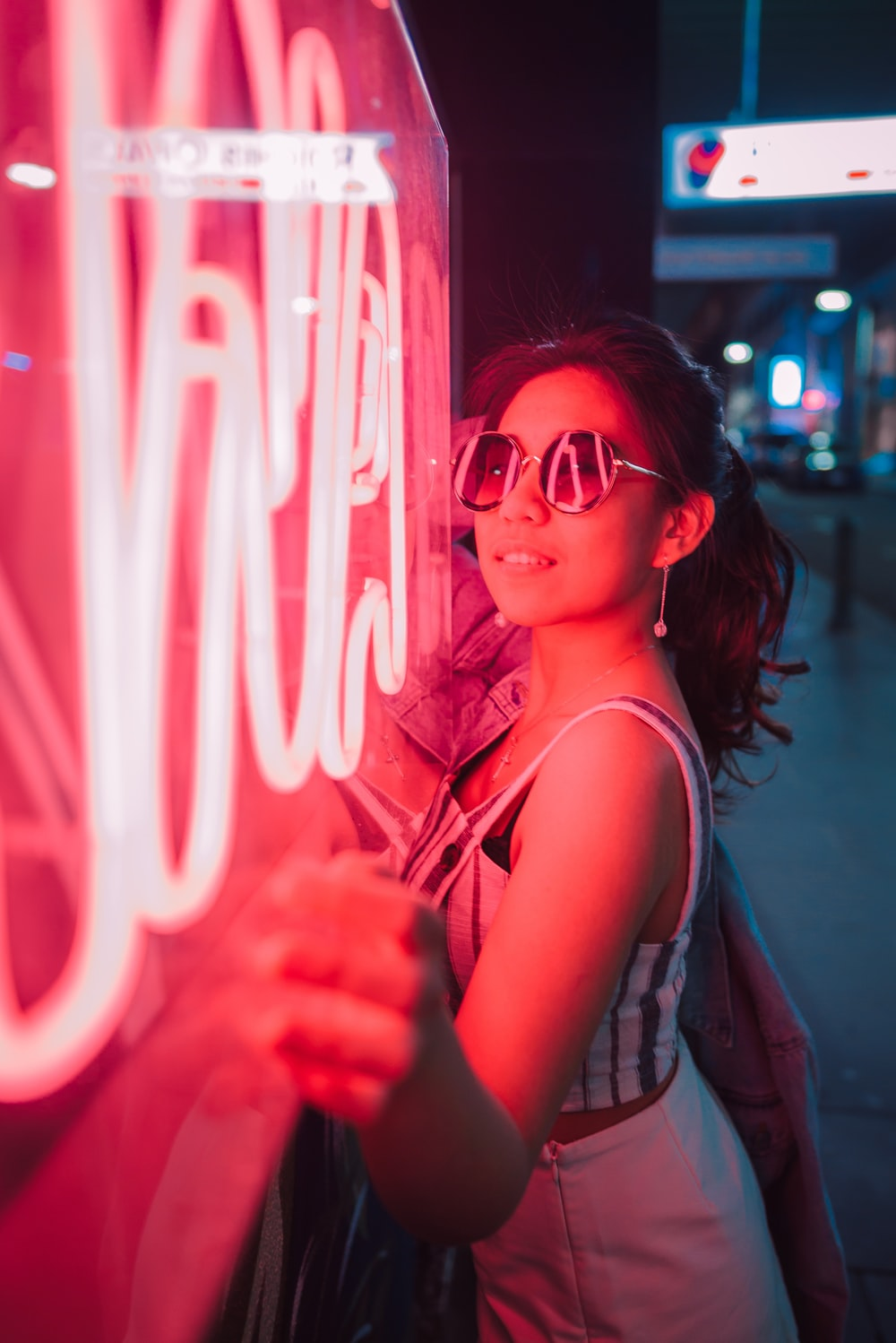woman standing near red neon signage at night