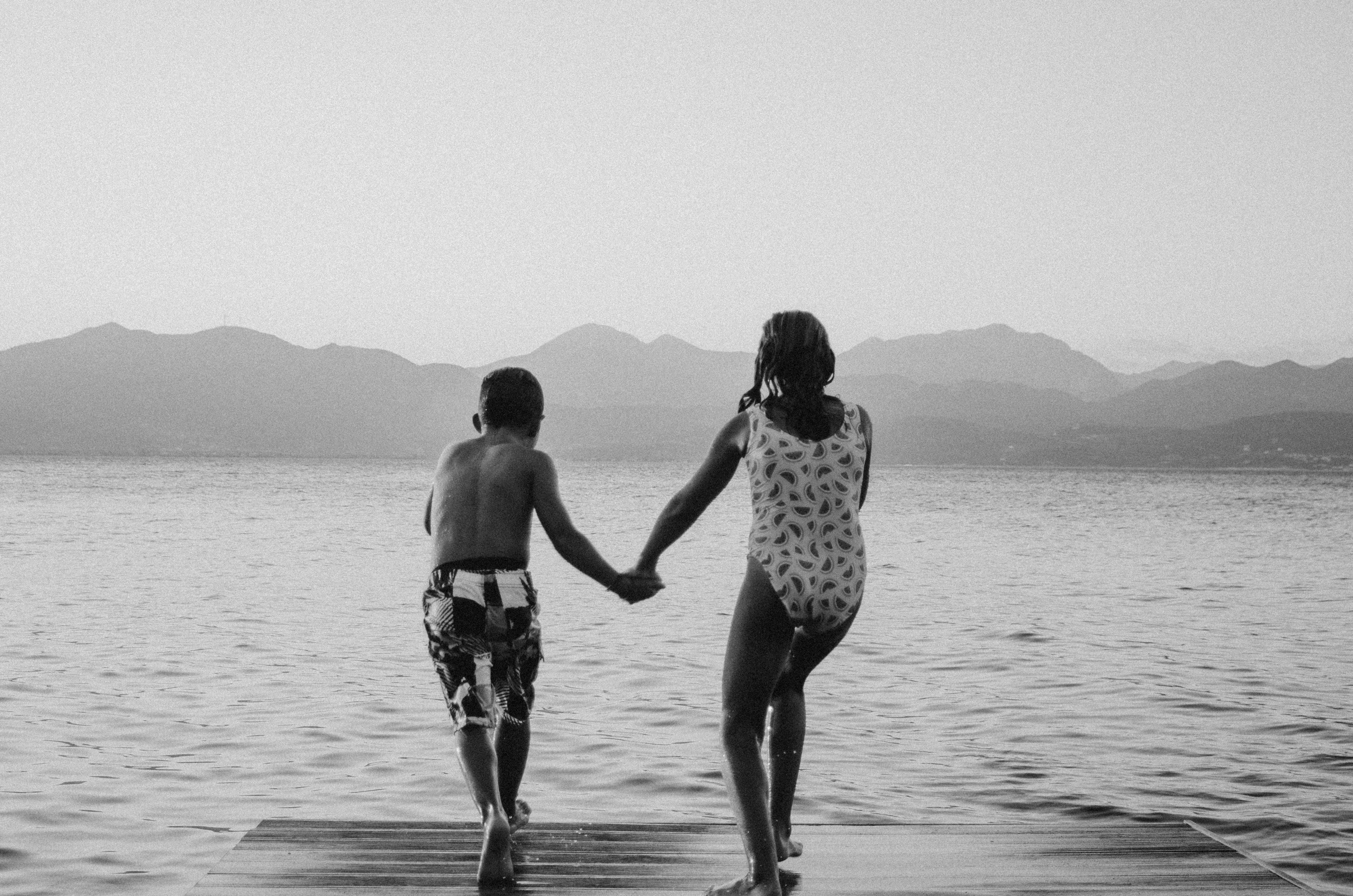 grayscale photography of girl and boy standing beside body of water