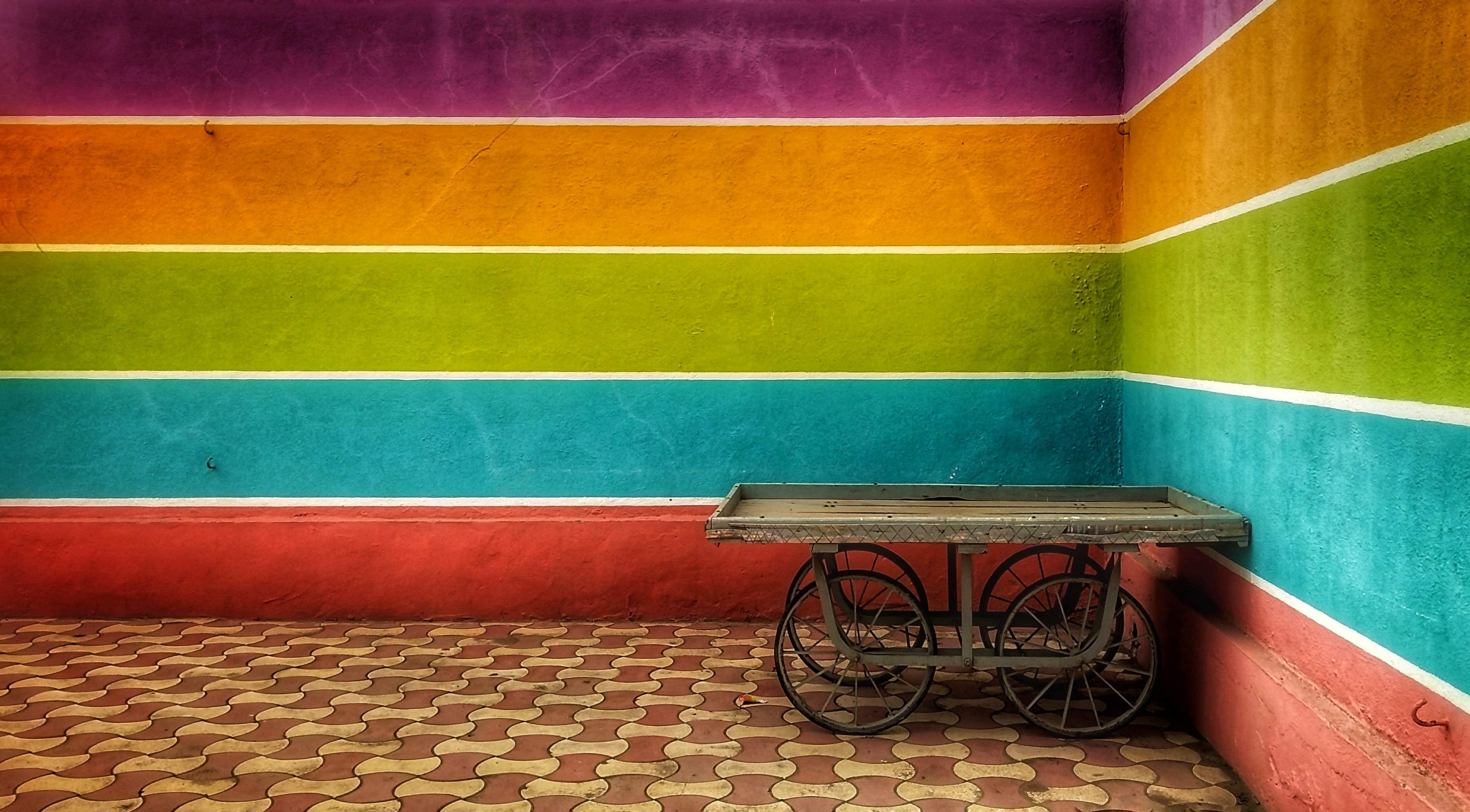 brown wooden bicycle cart near multicolored paint wall