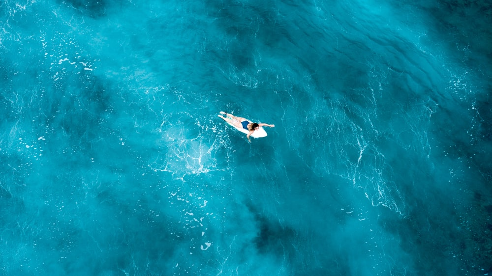 person on surfboard in midst of sea