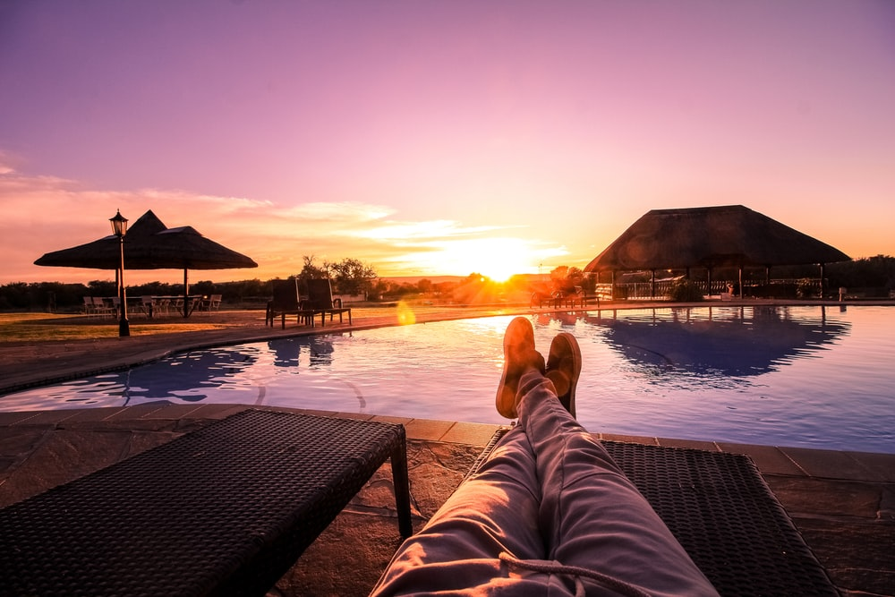 person lying on lounge chair facing at the swimming pool