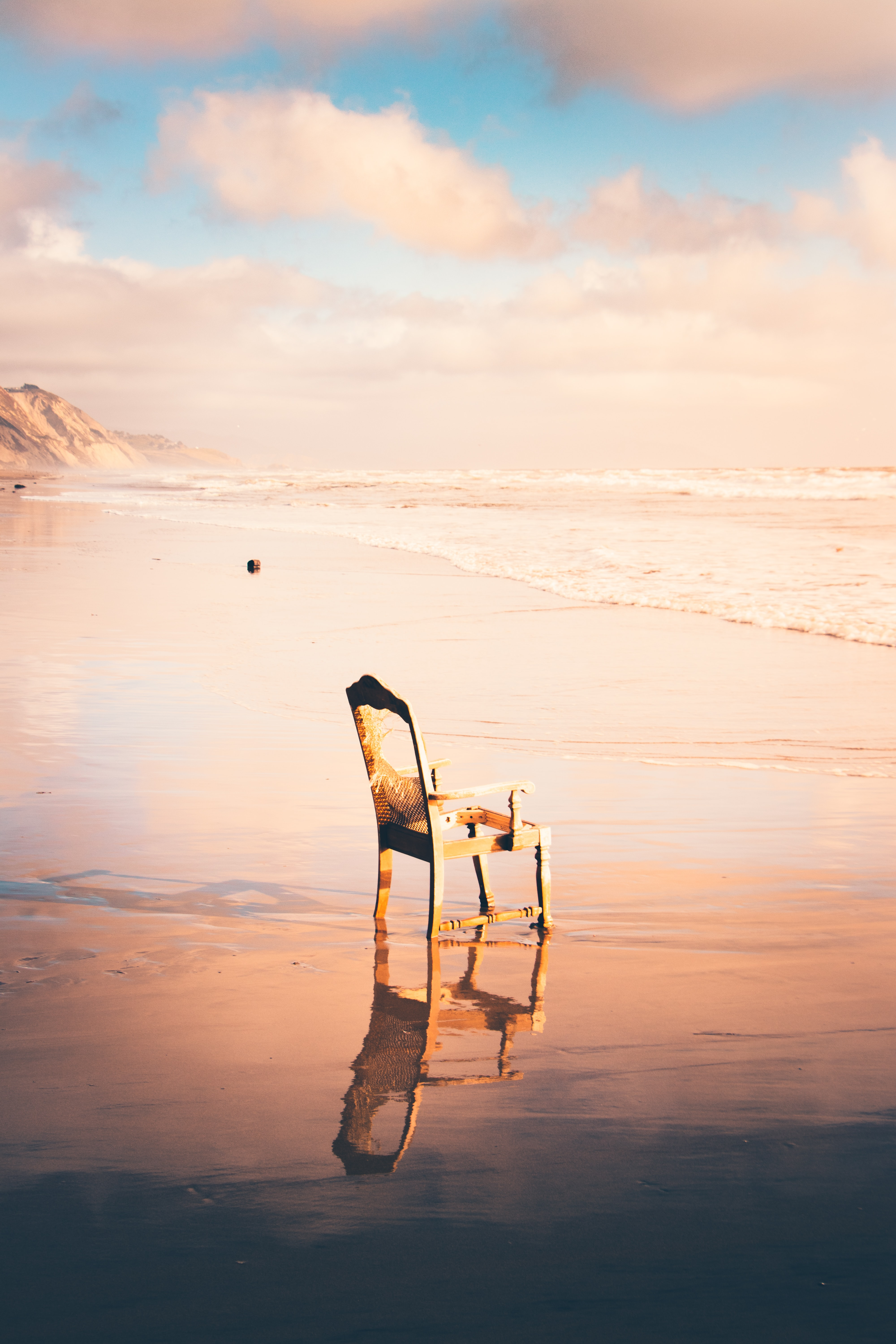 brown wooden armchair near the sea at daytime