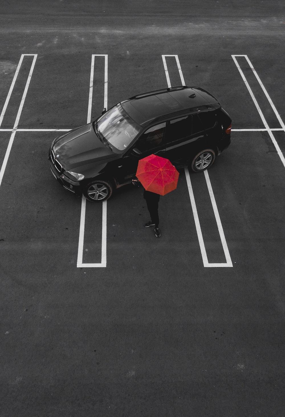 person holding red umbrella standing near black SUV