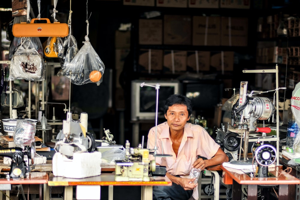 man sitting between two sewing machines
