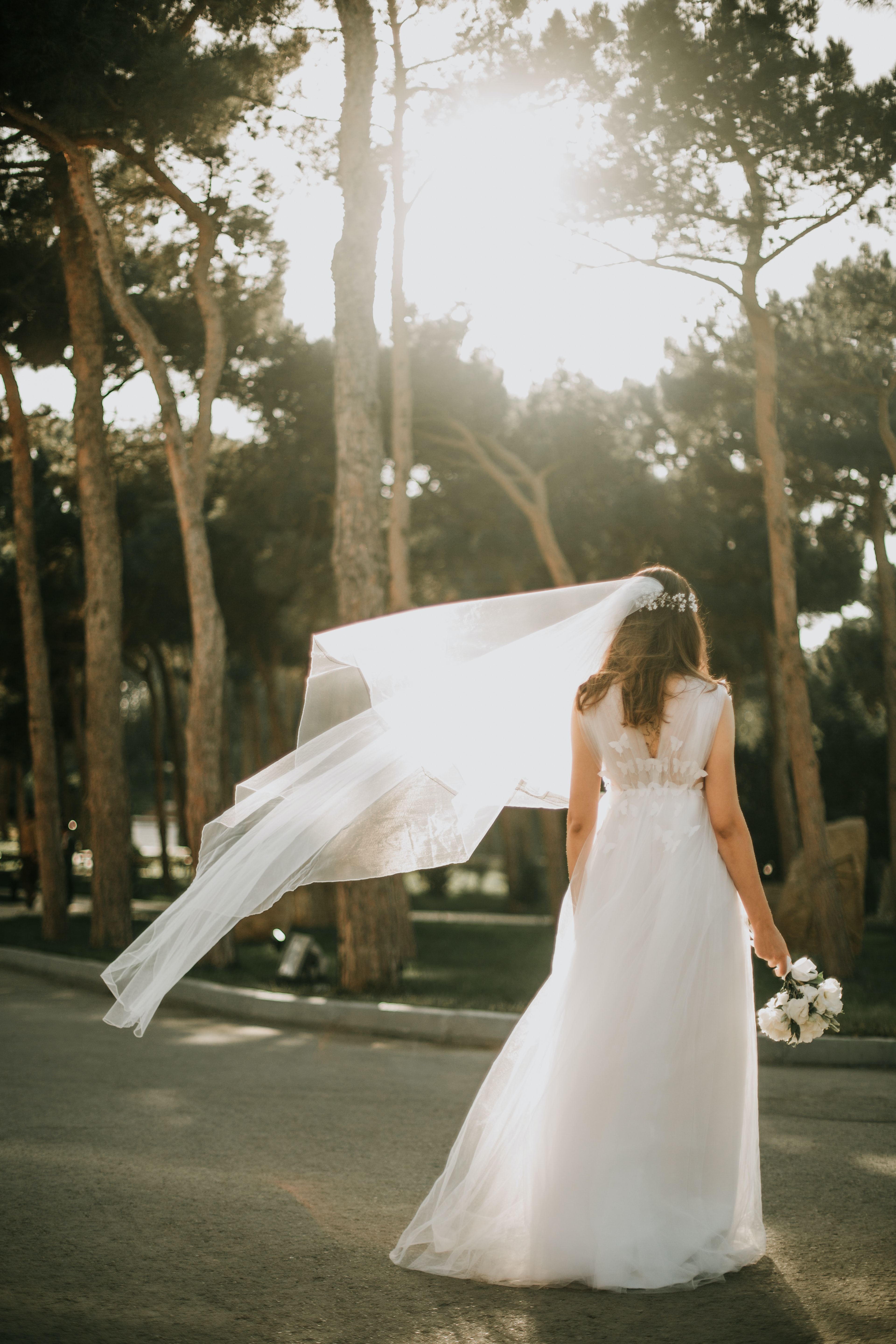 woman in white bridal gown standing on gray concrete