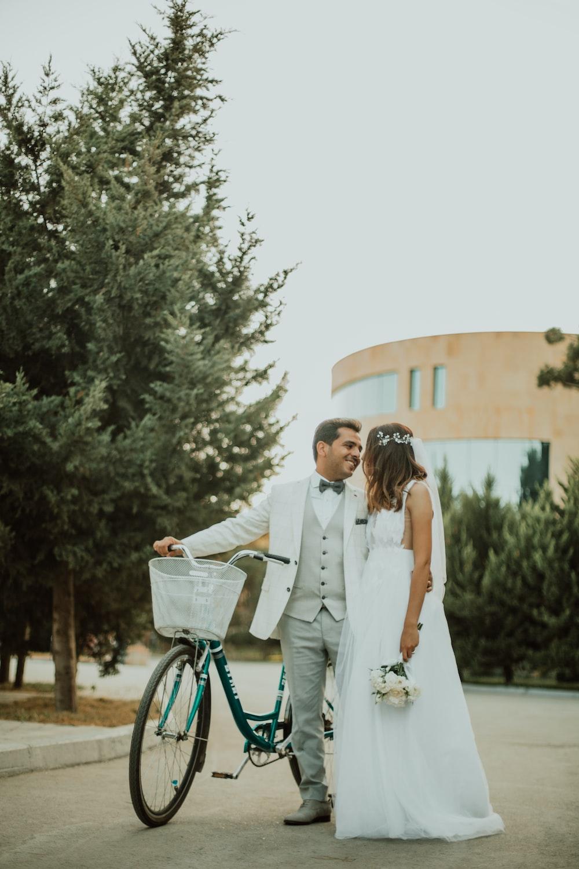 man and woman wearing wedding dress beside bicycle near tree during daytime