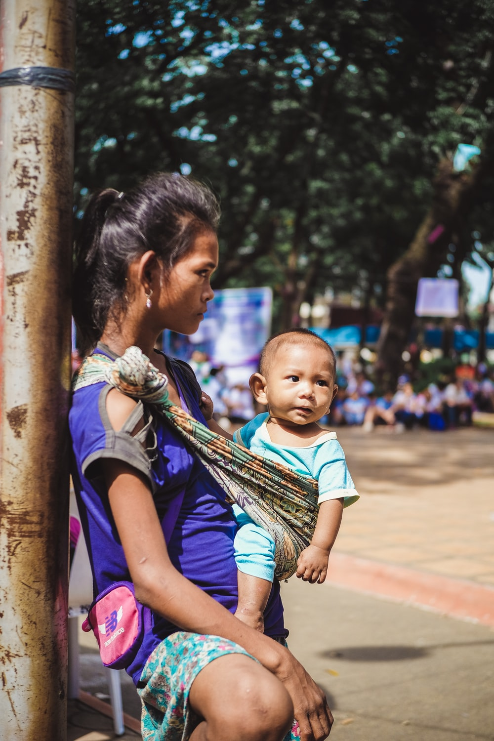woman carrying her baby while leaning against the brown wooden post