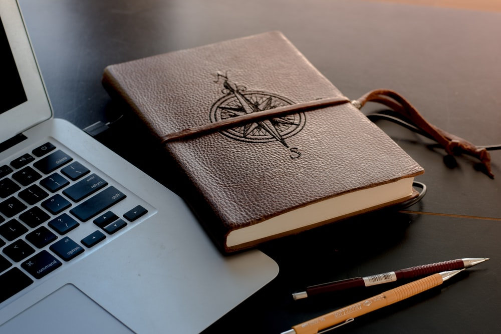 brown book beside MacBook