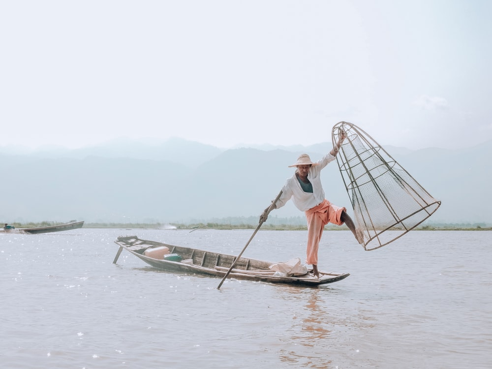 person holding fishnet standing on boat during daytime