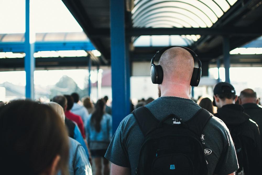 walking man wearing black wireless headphones near people