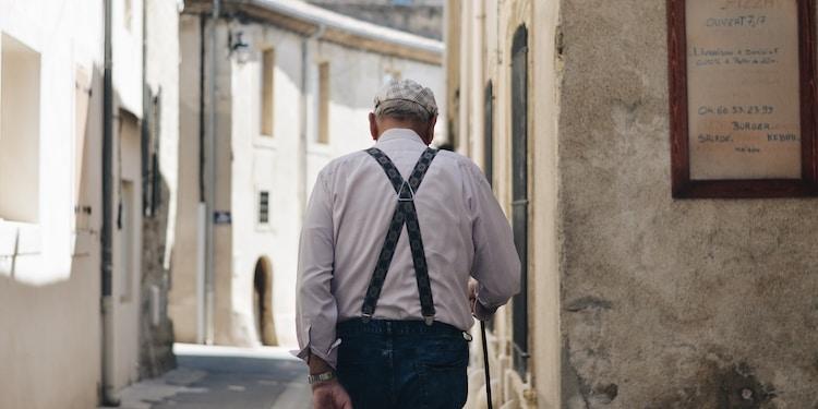 man standing beside white wall