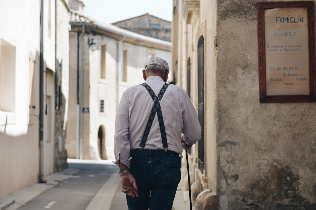 The back of the old man walking in the street