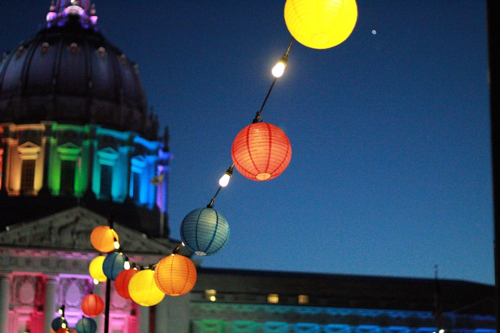 line of lighted lanterns in front of dome building during nighttime