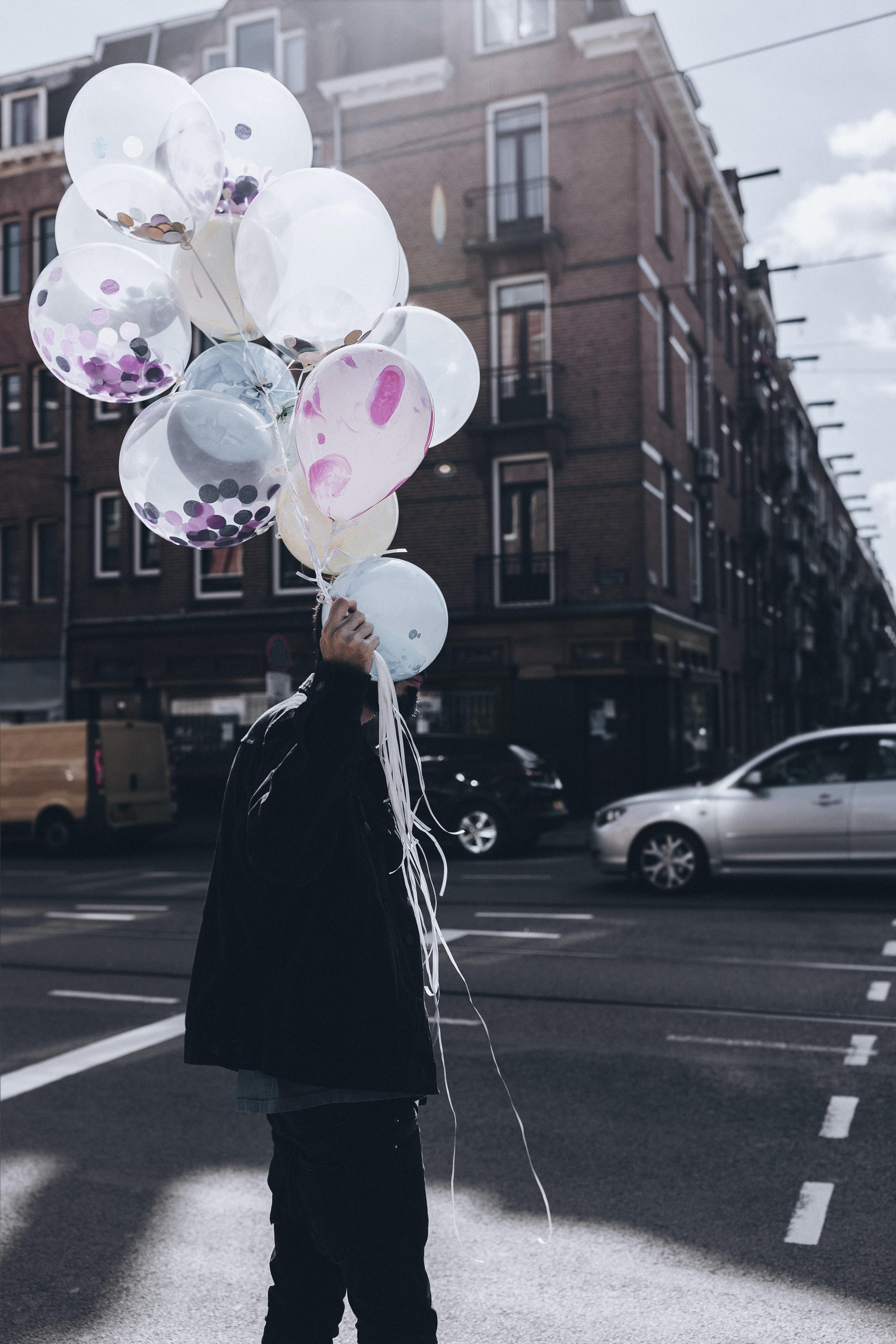 man holding white balloon walking on street during day time