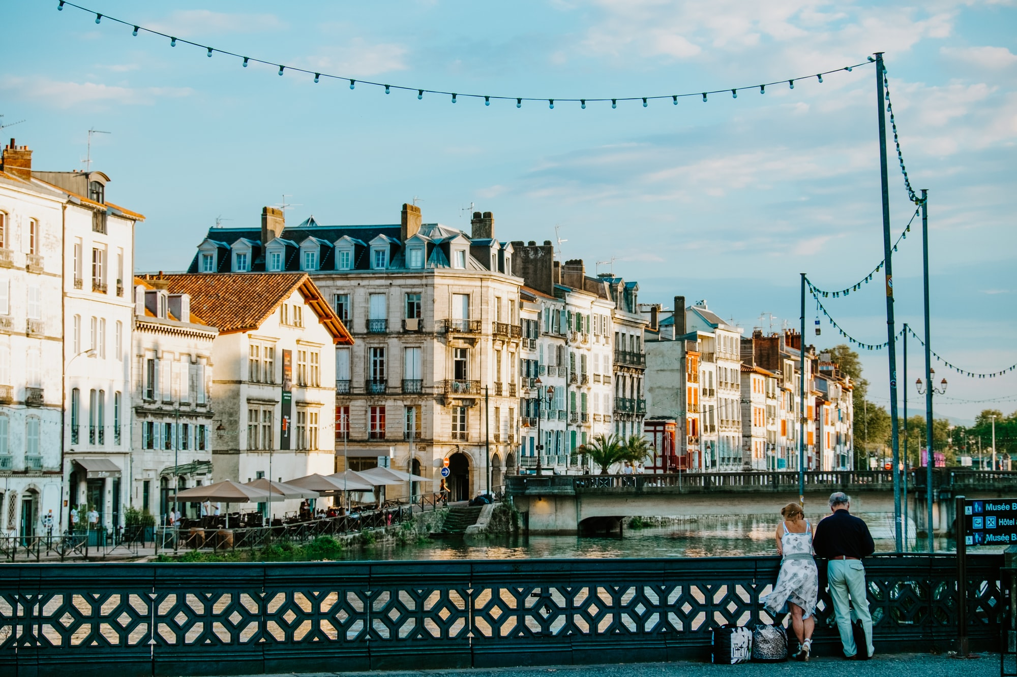 At 7:30 pm in early September there is a soft, golden light that hits the canal area of Bayonne, France and makes the old facades of the buildings glow.  A couple pauses on the iron bridge to admire the view.
