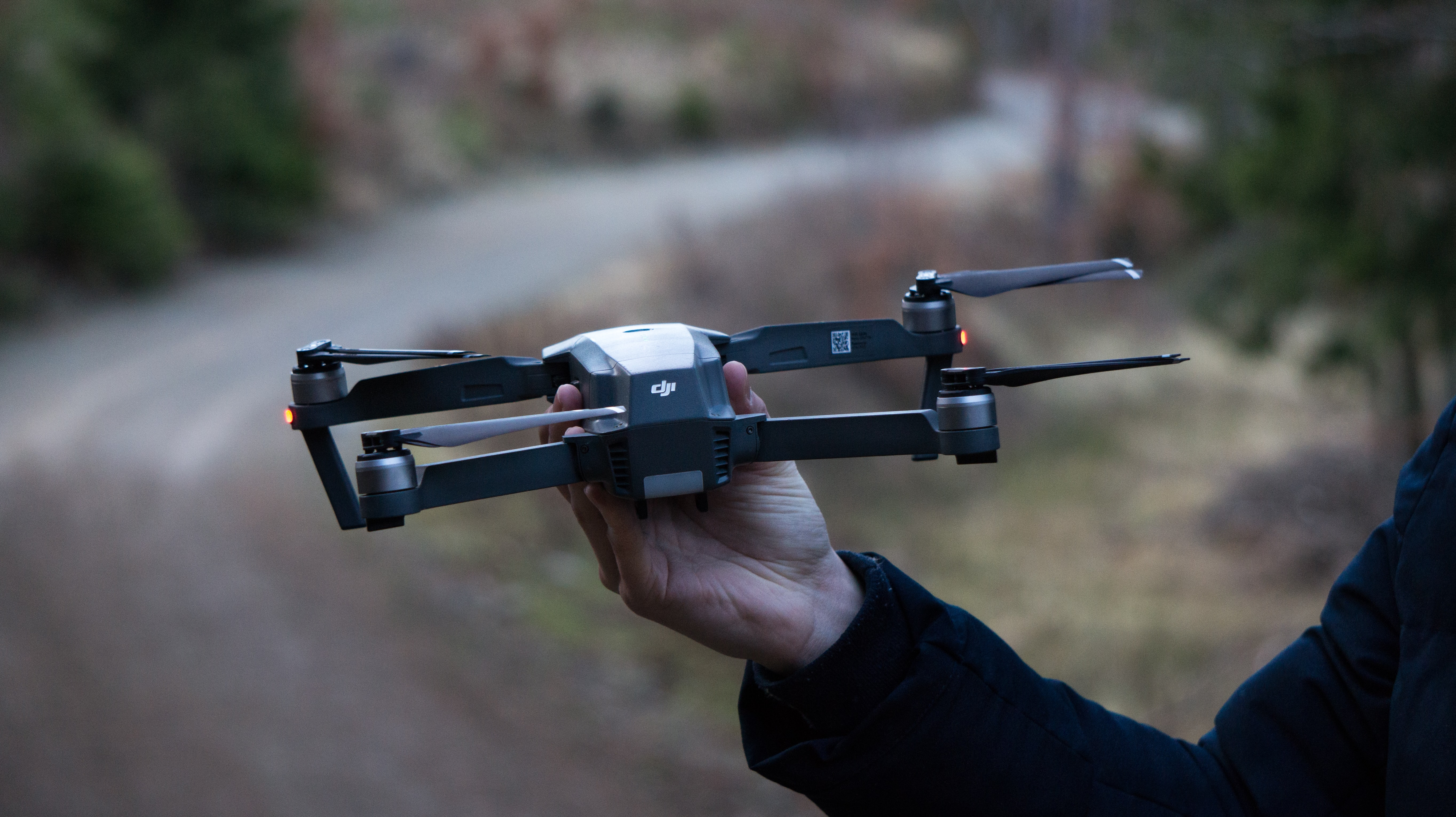 person holding black DJI drone