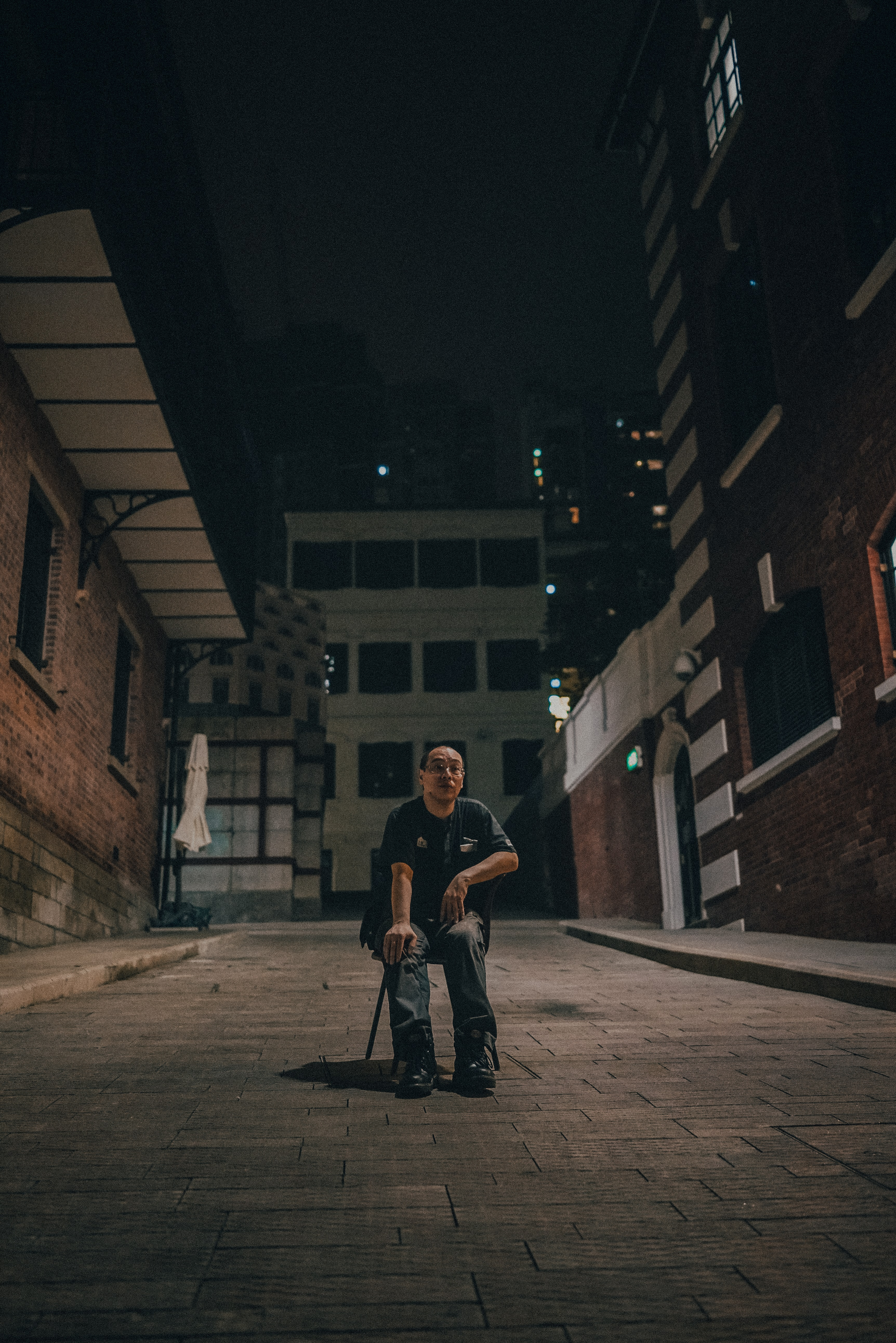man sitting on chair between brown brick buildings