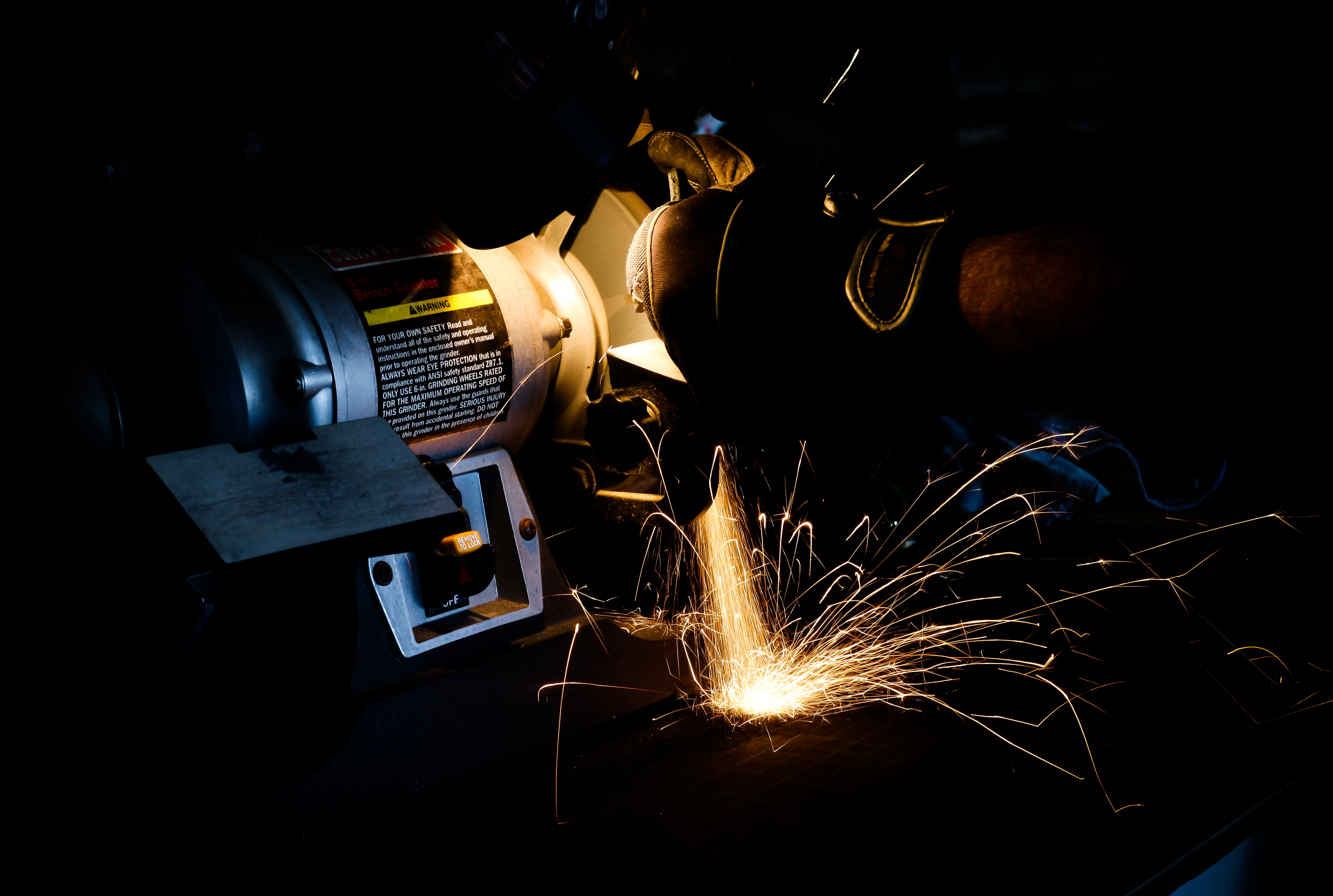 person using bench grinder