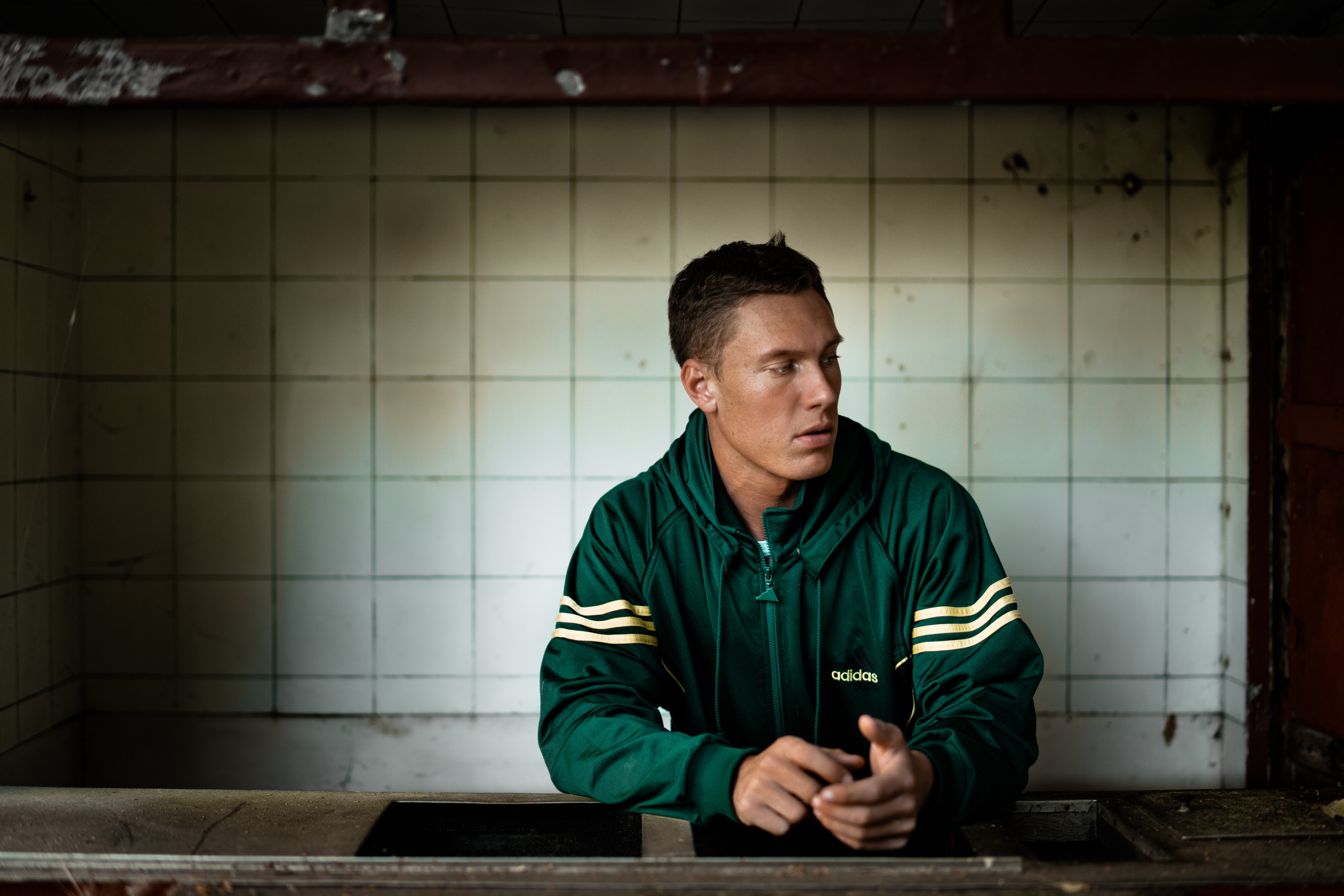 man in green zip-up jacket leaning on countertop