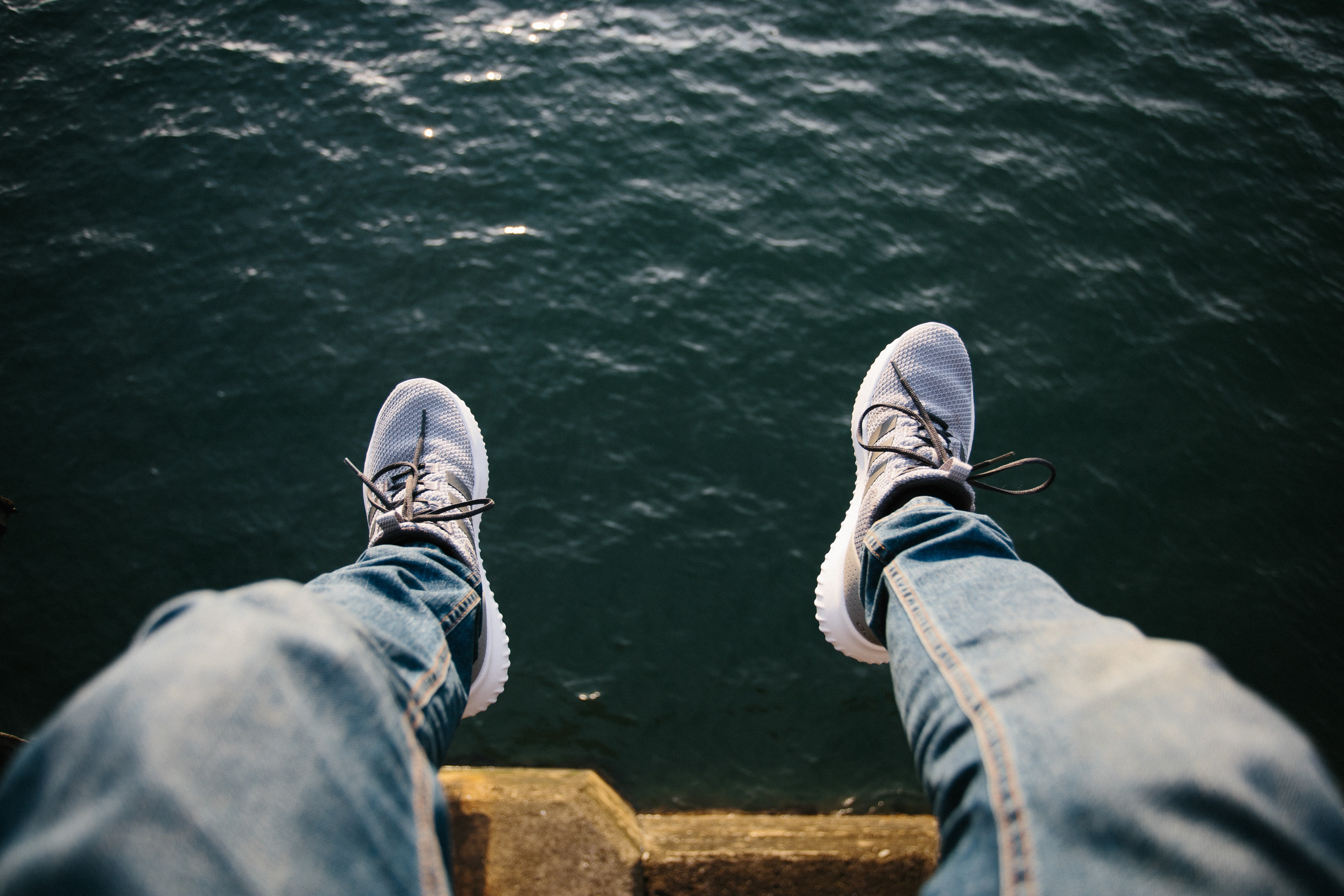 person sitting near body of water