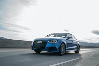 blue audi sedan driving on gray road audi zoom background
