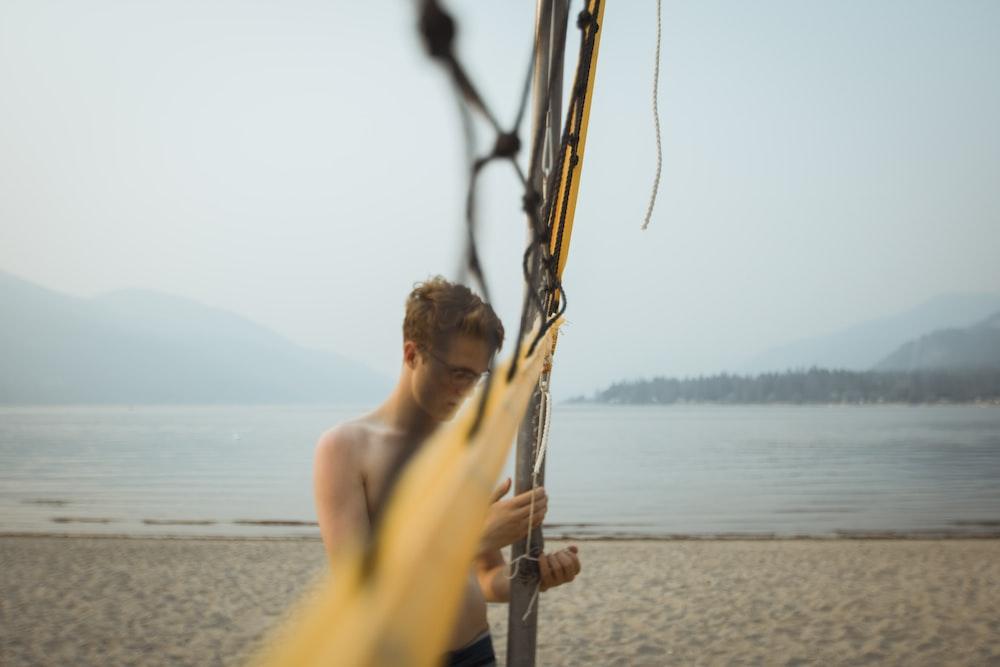 standing man beside net on beach during daytime