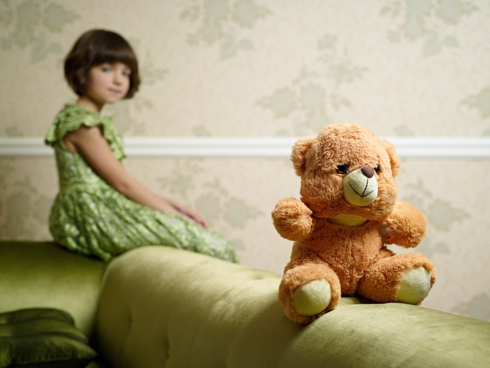 selective focus photography of brown bear plush toy on sofa