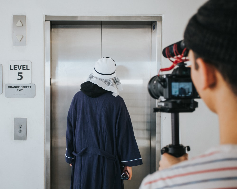 person filming man standing near elevator inside room
