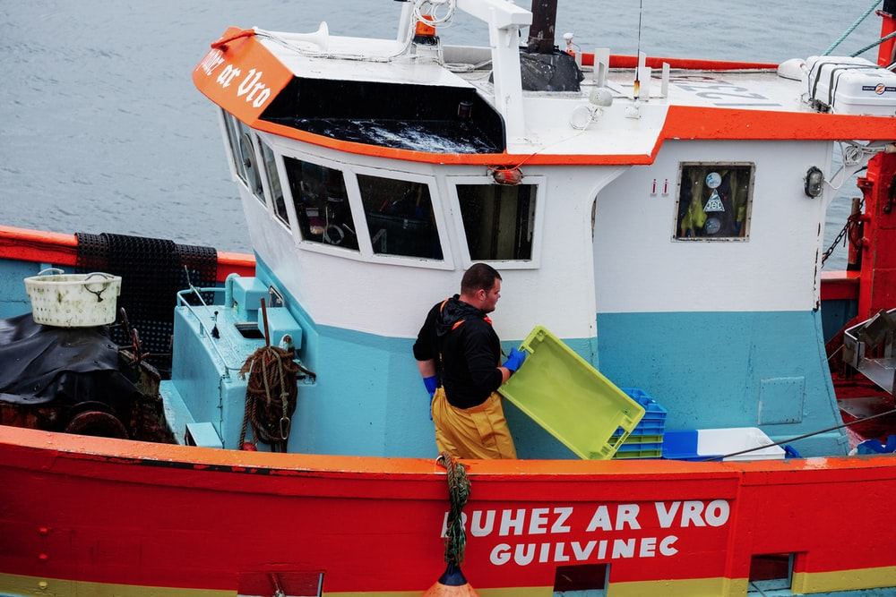 man standing on fishing boat holding green crate during day