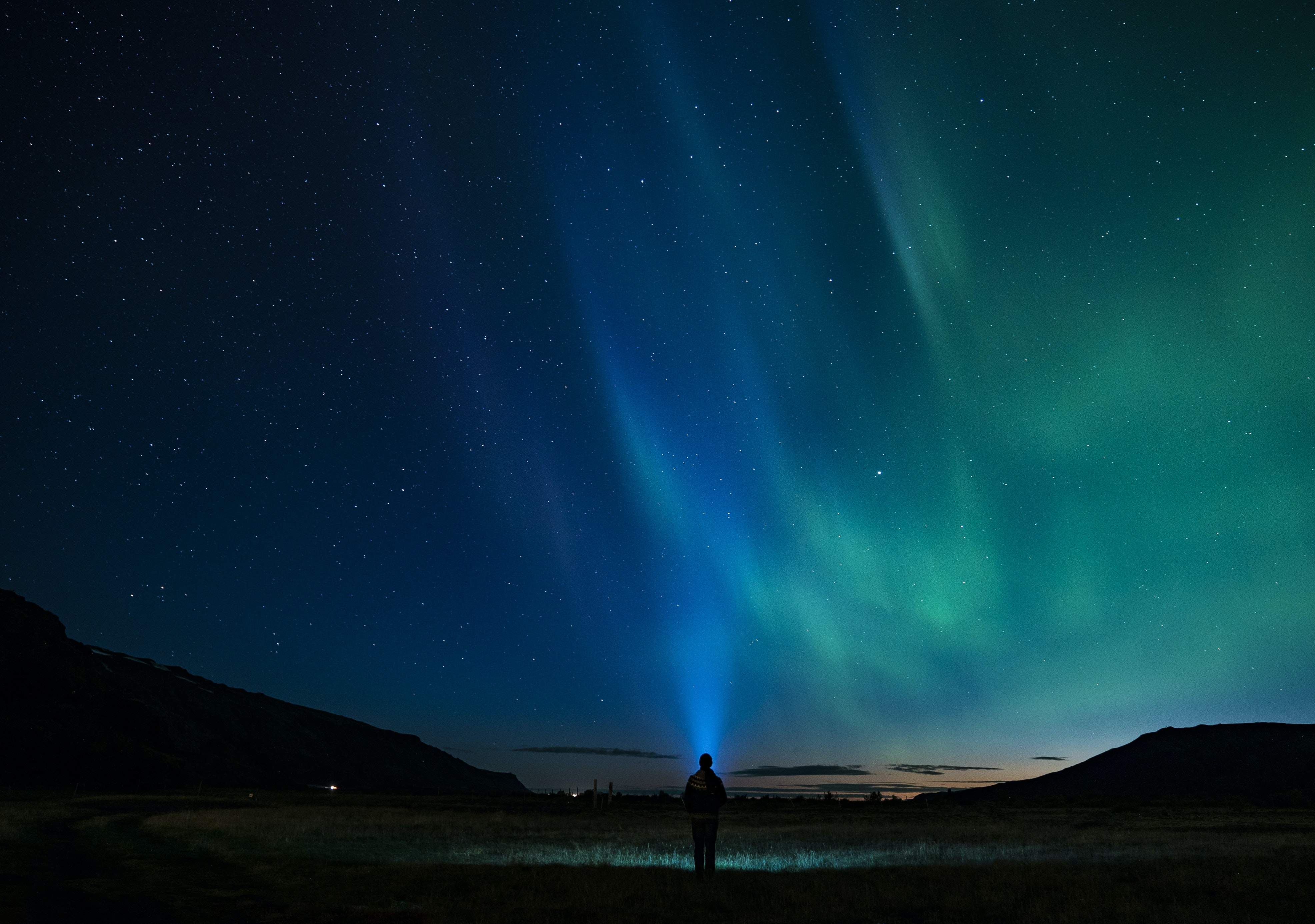 silhouette of person standing under aurora night sky