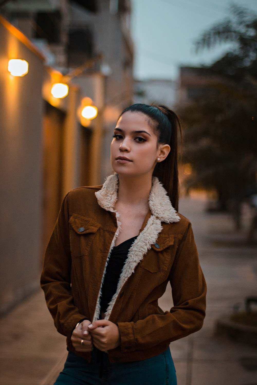 woman holding brown coat during daytime
